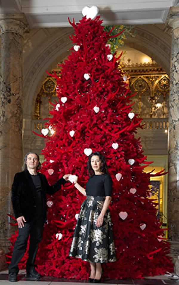 Helen and Colin David photographed in front of their 2013 V&A Christmas Tree - a red flocked antler tree