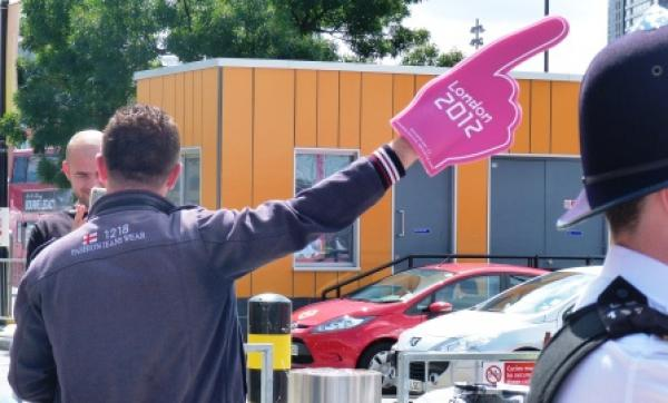 Man pointing with pink Olympic glove