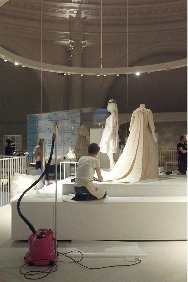 Wendy's dress is placed in the gallery, with preparations continuing around her. © Victoria and Albert museum, London