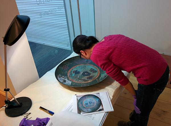Xiaoxin Li, Assistant Curator at the V&A, inspecting the condition of a 19th century dish during de-installation of the exhibition. © Victoria and Albert Museum, London.