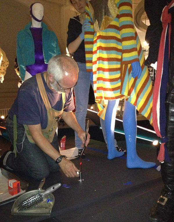 V&A technician Roger Hackett securing a Leigh Bowery ensemble to the plinth