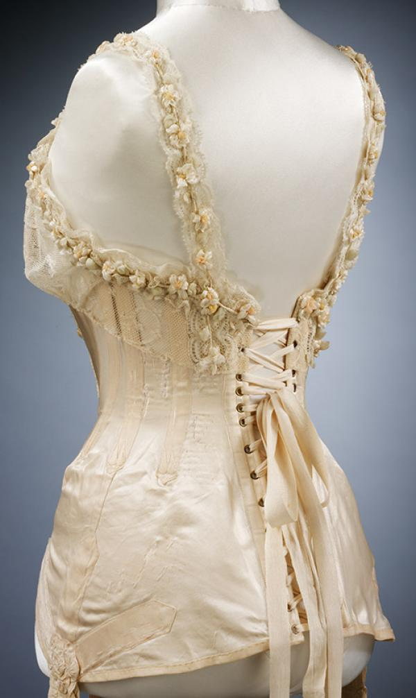 Corset for the wedding of Mrs G.E. Dixon in July 1905, satin trimmed in artificial orange blossom. © Victoria and Albert Museum, London