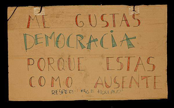 """I LIKE YOU, DEMOCRACY, BECAUSE IT IS AS THOUGH YOU ARE ABSENT"" (this placard is a play on Pablo Neruda's famous verse, ""I like you when you are quiet because it is as though you are absent""). Archivo 15M. CC"