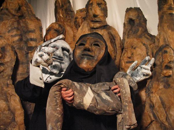 Puppet of an Iraqi woman holding a dead body followed by a puppet of a 'butcher'
