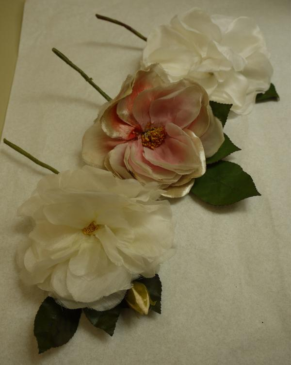 After treatment: 2 large artificial white roses and 1 pink camellia were reshaped with humidification using a small preservation steam pencil. Museum number T.49:2-2010. © Victoria and Albert Museum, London