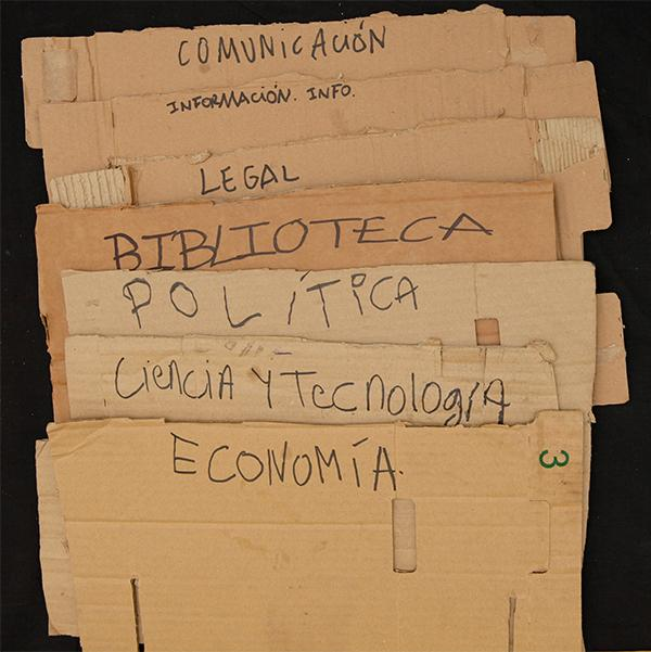 "Cardboard pieces marking the different discussion areas in the camp (""COMMUNICATION/ INFORMATION/ LEGAL/ LIBRARY/ POLITICS/ SCIENCE AND TECHNOLOGY/ ECONOMY""). Archivo 15M. CC"