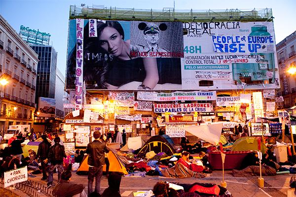 """Adbusting"" on a commercial. The banner in the centre reads: ""THEY DO NOT REPRESENT US"" Photograph by Julio Albarrán. CC"