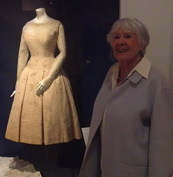 Laurel Robinson stands proudly in front of her wedding dress, on display at 'Wedding Dresses 1775-2014'. © Victoria and Albert Museum, London