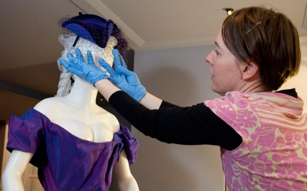 Senior Exhibitions Co-ordinator Sarah Scott installing the Stephen Jones hat that accompanies Dita Von Teese's bridal gown. © Museum of New Zealand Te Papa Tongarewa