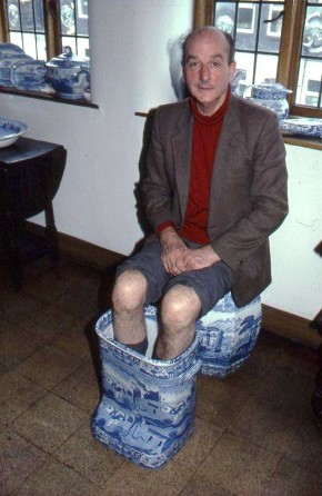 A man sitting on a ceramic seat with his feet in a large ceramic footbath