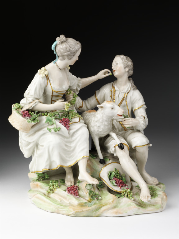 Figure group in soft-paste  porcelain, painted with enamels and gilded, of a male  youth and a girl offering each other grapes, made by William Duesbury & Co., Derby, ca. 1775. The grouping was adapted from an engraving by Jacques Phillipe Le Bas, after a painting by Boucher entitled 'Pensent-ils  au raisin?' V&A 414:423-1885