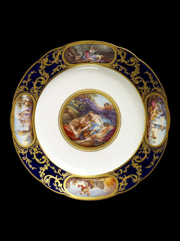 Soft-paste porcelain plate, painted in enamels and gilt,  made by Sèvres porcelain factory, France, about 1785. The central scene 'Les Bacchantes endormies',  was taken from an engraving by Rene Gaillard, after Francois Boucher. V&A C.452-1921