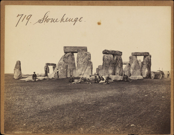 Black and white photograph of Stonehenge showing people sitting on the stones.