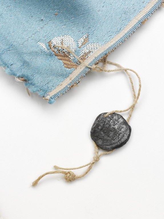 An 1813 lead customs seal attached to the corner of a silk furnishing fabric, woven by Jean Pierre Mazer, Stockholm, 1813.