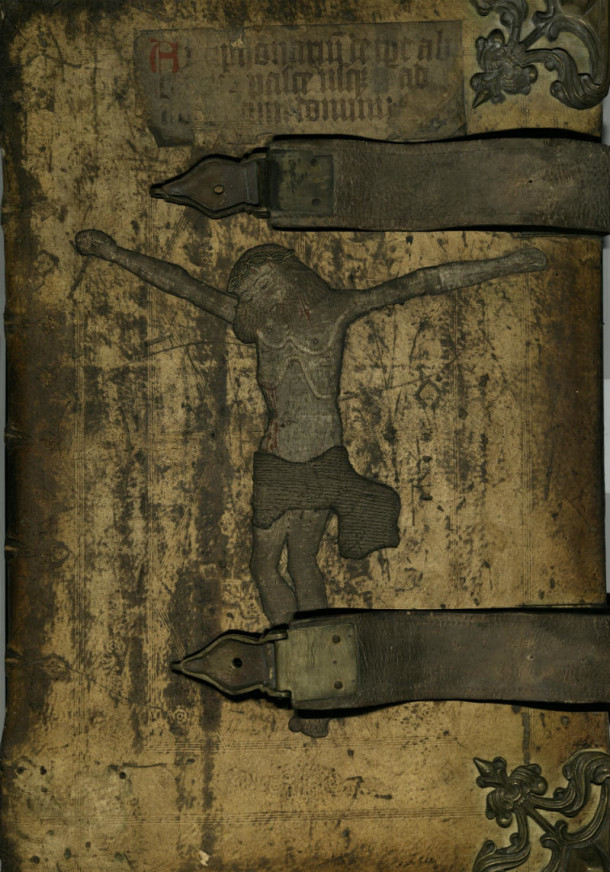 [Antiphoner cover.] German binding, ca. 1500. Buckskin; blind tooling; embroidered figure of Christ crucified; metal mounts; 2 large leather buckles with animals' heads; original title written on a strip of vellum. NAL pressmark: Drawer 105