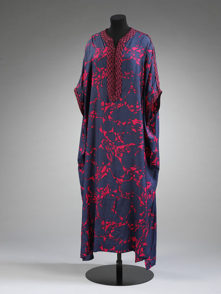 Female gandura (a garment that was initially only worn by men before Moroccan fashion designers introduced it for women in elegant fabrics and colours), made of a fluid printed silk and decorated with characteristic loop braids called sfifa. Designed by Naima Bennis, c. 1970. V&;A: ME.16-2015