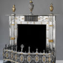 Fireplace with fender, mantel ornaments, and fire-irons, of burnished steel with applied decoration of gilt copper and brass and cut steel.