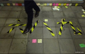 """The tape on the floor at Lennon Wall's staircase reads """"689"""" in Chinese, a nickname of the city's Chief Executive CY Leung. Leung won the Chief Executive election in 2012 with 689 votes from the 1,200 member election committee.©Becky Sun"""