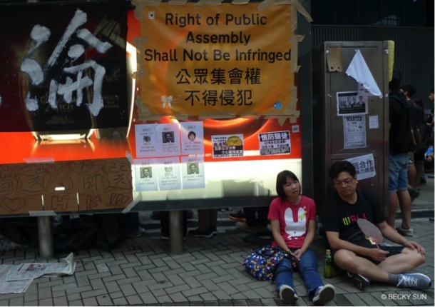 The yellow banner is a spoof on a similar yellow warning sign the police commonly use asking for protesters to retreat.