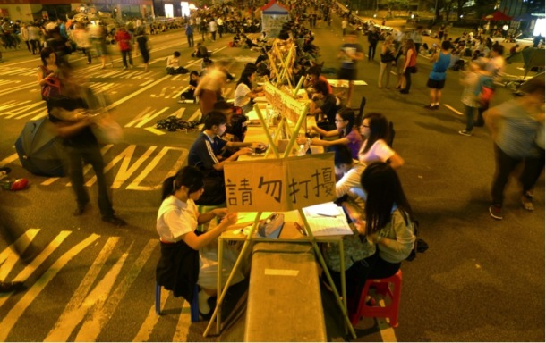Study corner in early October, designed by teachers and students from the Polytechnic University. The workstations were built along a concrete road barrier on Connaught Road, Admiralty, adapted from salvaged wood planks and stools from around the site. The study corner has been expanding ever since.  Photograph by Becky Sun.  ©Becky Sun.