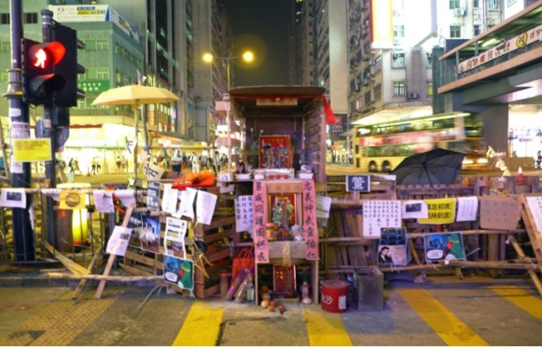 A Kwan Tai temple set up along a barrier in Nathan Road, Mong Kok. Kwan Tai is a warrior god revered by police in Hong Kong as well as allegedly triad members who are said to have a stake at the district. The temple was removed in the police action on 17 October.  ©Becky Sun