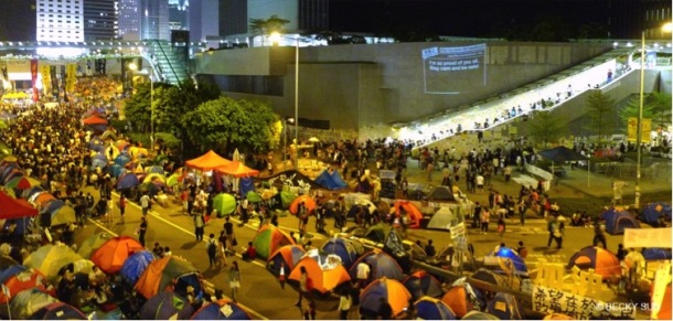 """Around 2,300 tents have been propped up around the Central Government Offices in Admiralty, Hong Kong. The wall projection is """"Add Oil Machine for HK Occupiers"""" by artists including Sampson Wong Yu-hin and Jason Lam, which displays support messages collected via a website they custom built. Photograph by Becky Sun. © Becky Sun"""