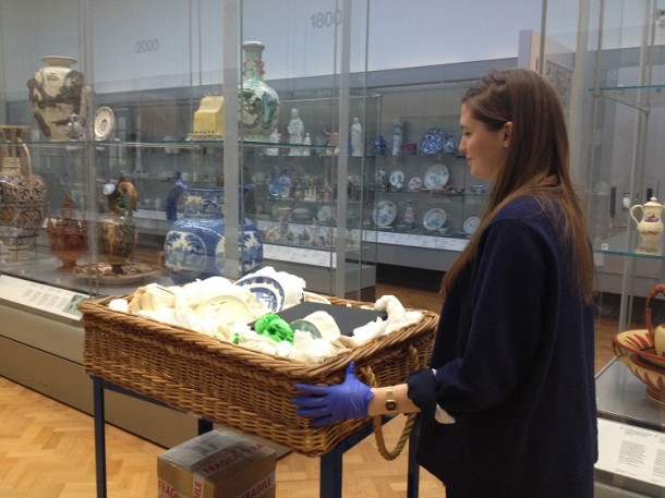 Florence pushing a trolley of objects through the gallery