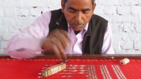 Meharban Khan doing gota work in the workshop on his roof