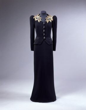 T.399&a-1974 Elsa Schiaparelli, Dress and Jacket with gilt embroidery. Ensemble previously mounted on a torso dress stand.