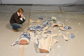 A man crouches by a pile of smashed blue and white ceramic pieces