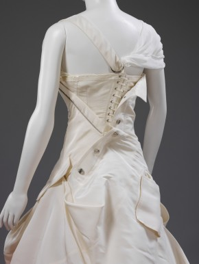 The corset fastenings on the back of the dress's bodice are left exposed