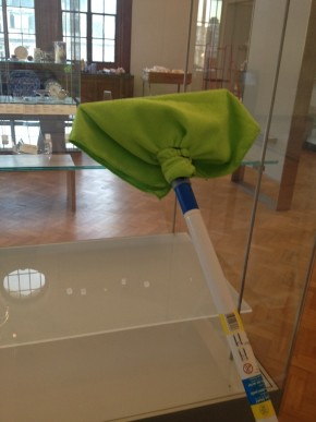 A squeegee cleaning stick with a green cloth attached