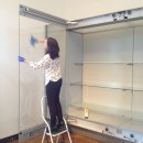Curator Rebecca Wallis stands on a stepladder cleaning the wall case