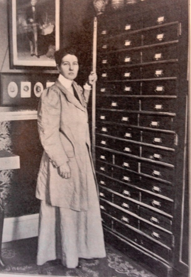 Enthoven at home with cabinets holding her collected materials, about 1909.