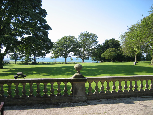 Sea view with trees and lawn in foreground