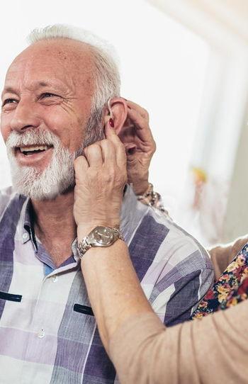 donna aiuta un anziano signore a indossare l'audioprotesi