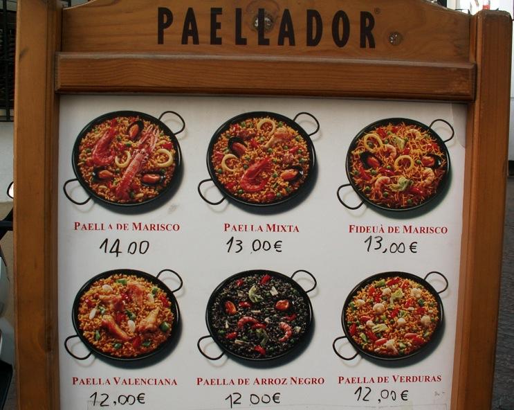 ¿Te suena este cartel? ¿Dirías que la paella valenciana de la foto se parece a alguna de las que conoces?