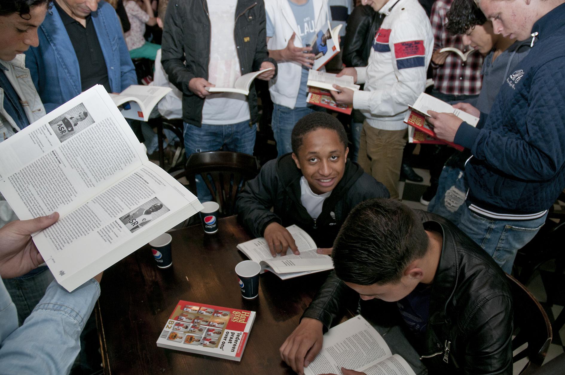 De jongens van 'Onder 16' hebben een exemplaar van 'Iedereen praat over ons' uitgereikt gekregen. Rechtsonder Calvin Verdonk.