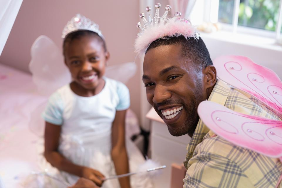 """Cheerful father and daughter wearing costume wings at home"" stock image"
