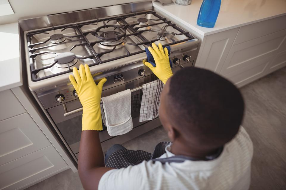 """Man checking gas stove in kitchen"" stock image"