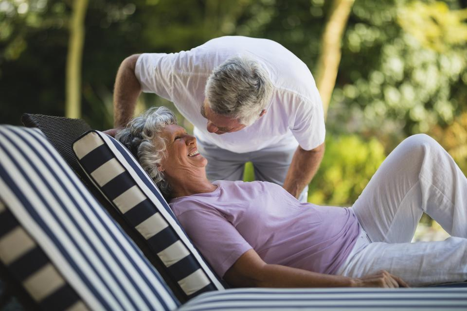 """Senior man bending over woman resting on lounge chair"" stock image"