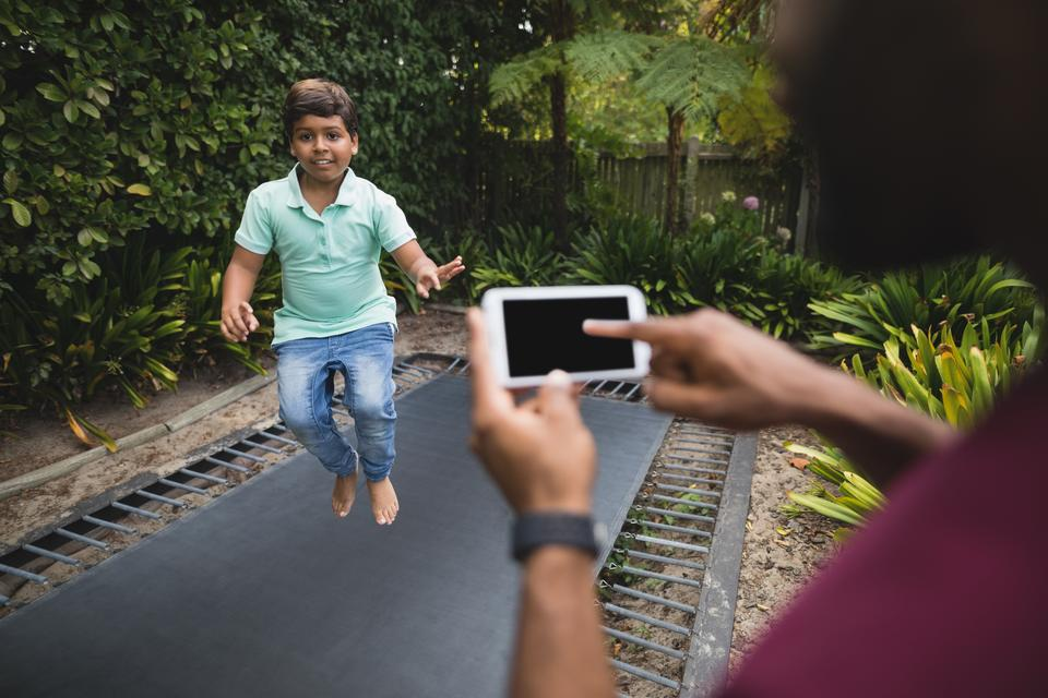 """Father photographing son while jumping on trampoline at park"" stock image"