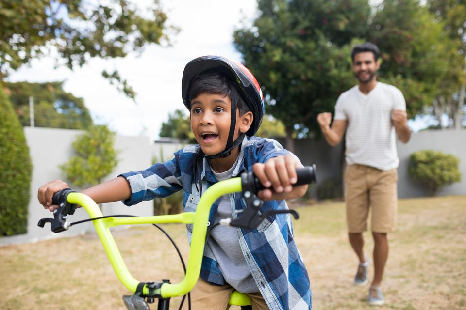 """""""Boy cycling with father standing in background"""" stock image"""