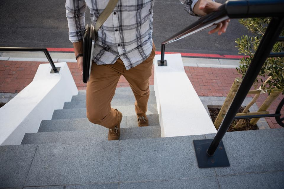 """Man moving up on steps"" stock image"