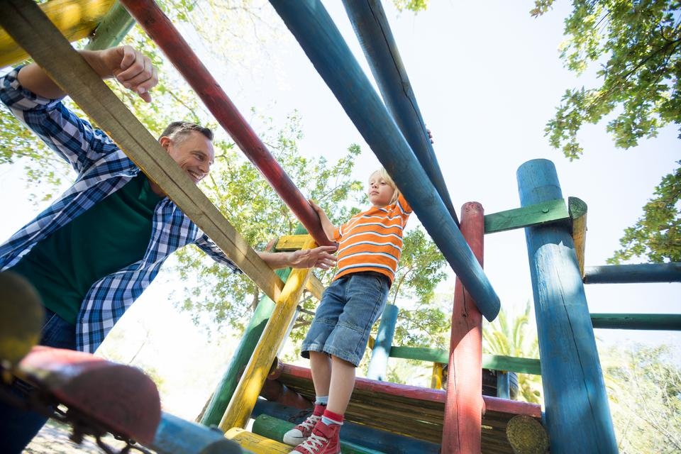 """Father looking at son walking on jungle gym at playground"" stock image"
