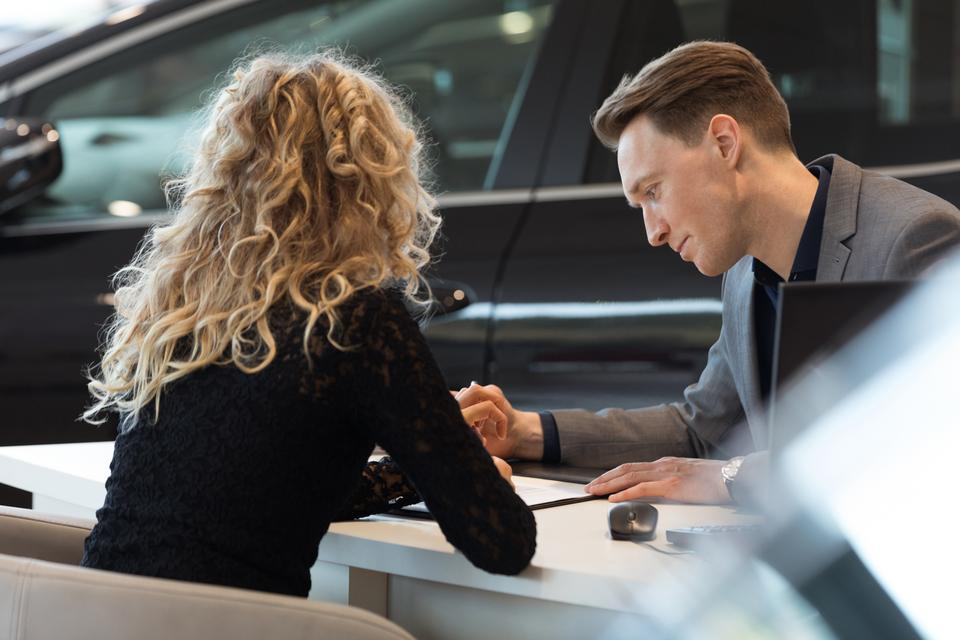 """""""Car salesperson talking with customer in showroom"""" stock image"""