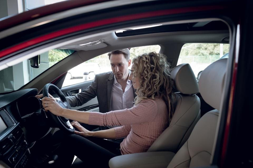 """""""Salesperson assisting woman sitting in car"""" stock image"""