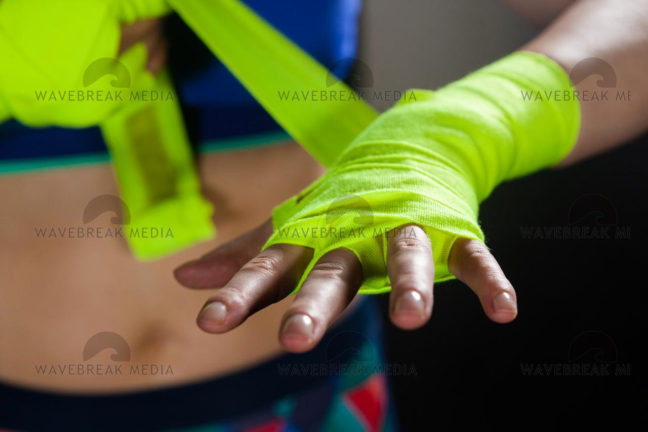 """""""Mid section of woman tying hand wrap on hand"""" stock image"""