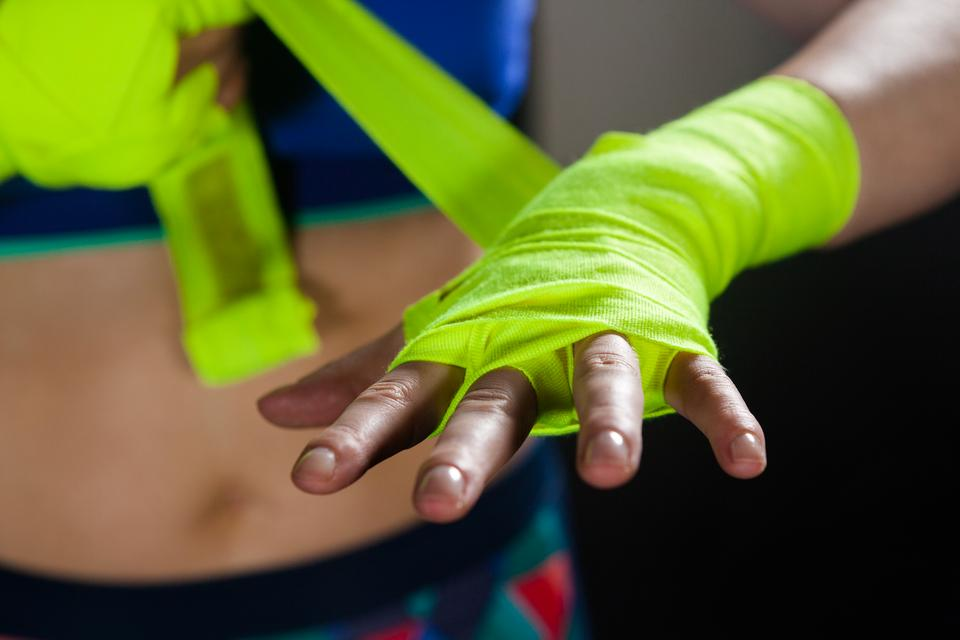 """Mid section of woman tying hand wrap on hand"" stock image"