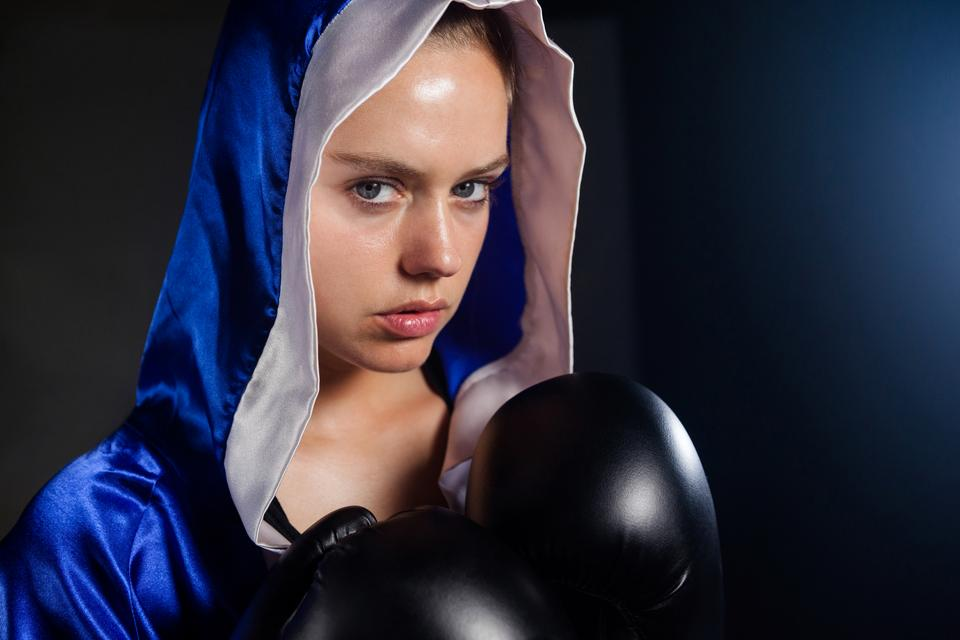"""Determined woman wearing boxing gloves"" stock image"